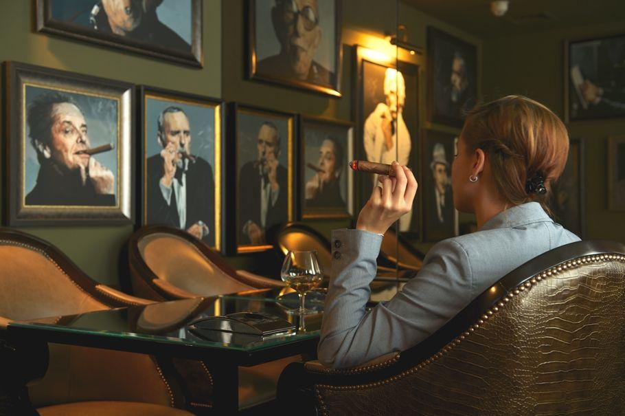 A person is enjoying a fine cigar in their cigar room.