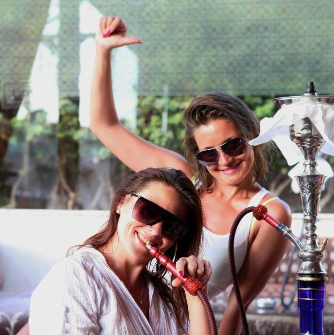 Happy women smoking hookah pipes in fort lauderdale Miami.