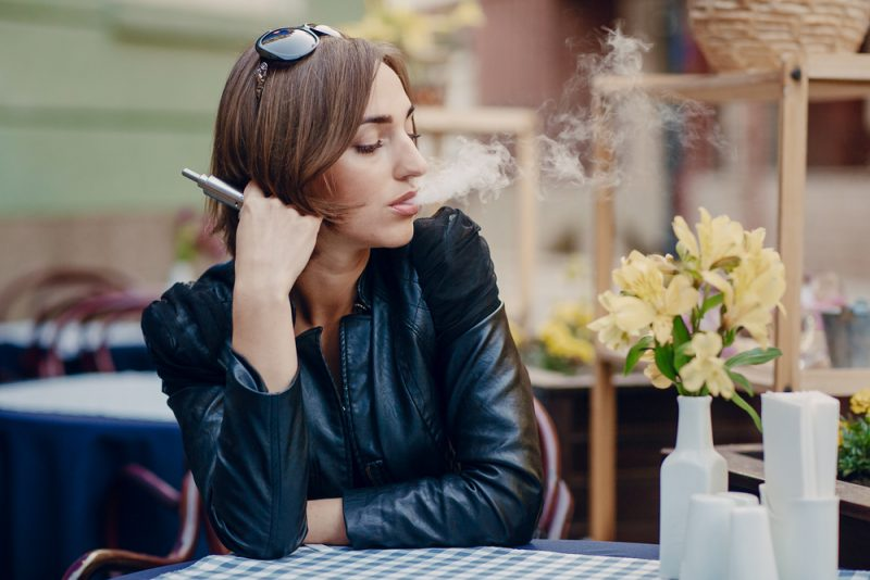 Image of a girl vaping in a restaurant.