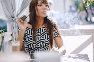 Woman smoking an e cigarette in a restaurant.
