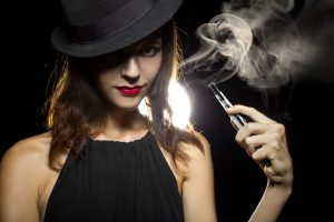 Attractive woman vaping dry herbs