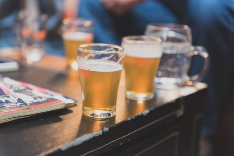 A photo of several glasses of beer in a bar.