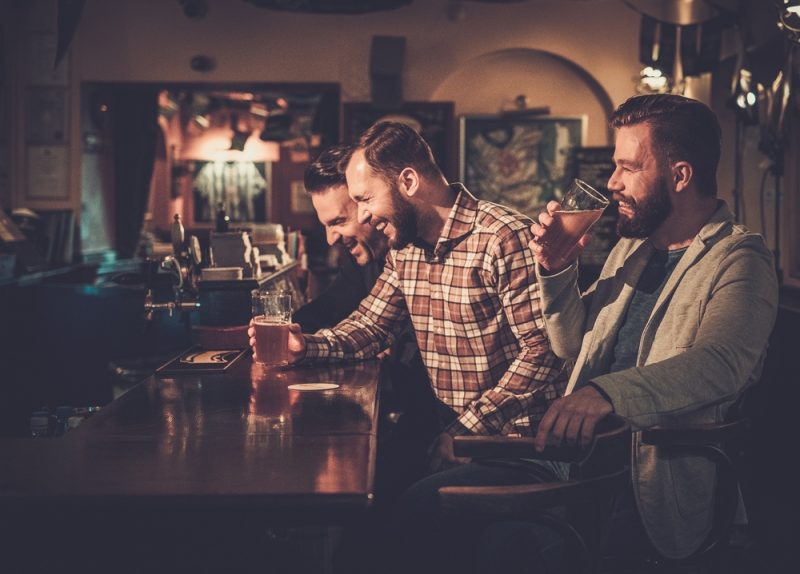 Men in a bar drinking and enjoying a bachelor party.