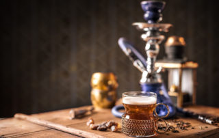 Still life of black tea in glass cup on wooden table, hookah in background