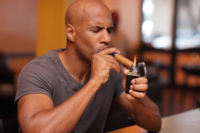 Image of a mature male lighting his cigar