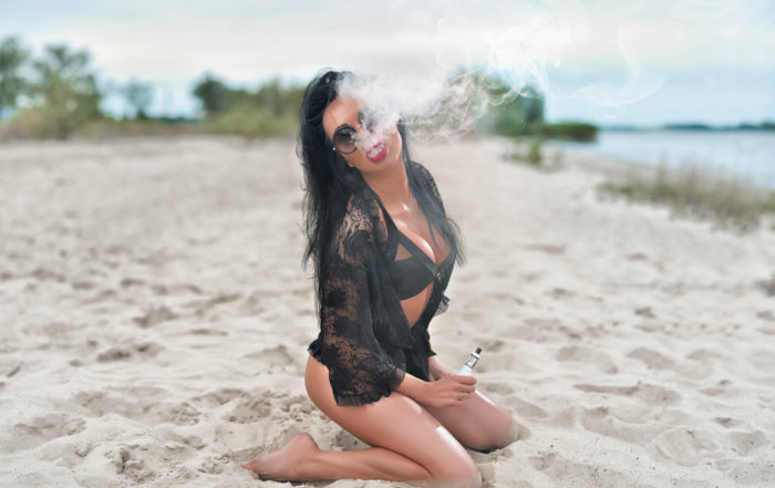 Image of Brunette girl on the beach in Miami. Concept of cool vape accessories and which ones you need.
