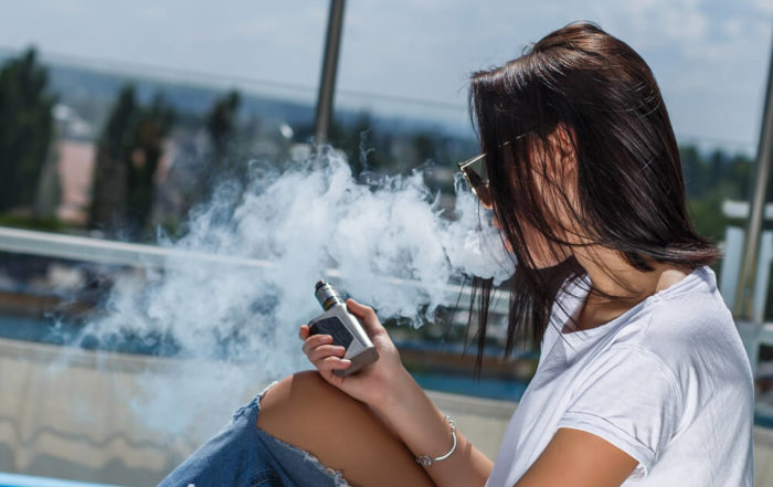 Young woman vaping - 5 Pros and Cons of Vaping